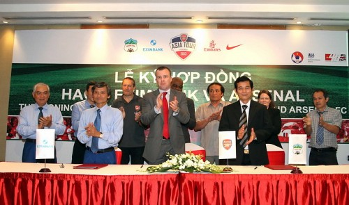 Arsenal marketing director Angus Kinnear, who wears a red tie, is seen during the signing of an agreement in Hanoi on Arsenal's July visit to Vietnam in this May 9, 2013 photo.