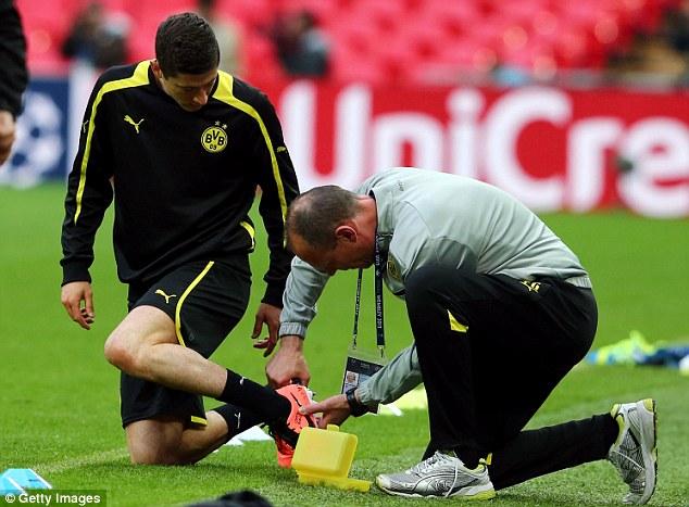 Running repair: Prolific Dortmund striker Robert Lewandowski gets his boot fixed