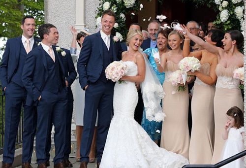 Family affair: The couple's wedding party showered them with petals outside the church