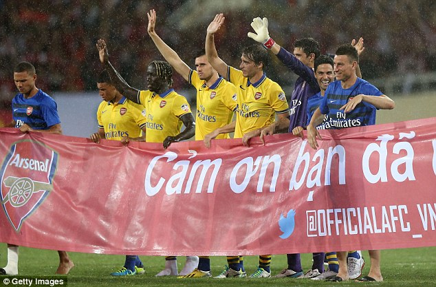 Thanks! The Arsenal players carry a 'Thank You' banner and wave to fans after defeating Vietnam