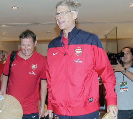 Hats off to Wenger: Arsenal coach Arsene Wenger and his players arrive in Ha Noi yesterday morning. — VNA/VNS Photos Quoc Khanh