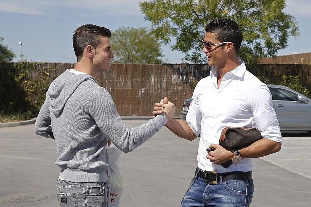 """Trước khi bước vào sân tập, Bale tái ngộ Cristiano Ronaldo, cầu thủ vừa bị chính Bale """"hạ bệ"""" trên danh sách Guinness về chuyển nhượng. Kỷ lục 94 triệu euro do CR7 lập bốn năm trước đã trở thành quá khứ."""