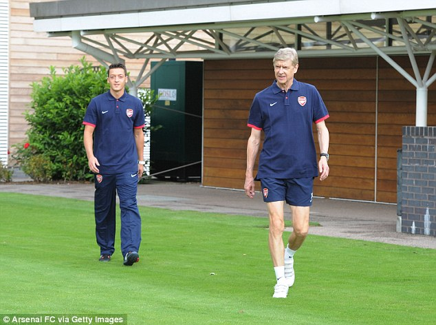 Welcome to London: Arsene Wenger leads Mesut Ozil out on to the training ground at London Colney
