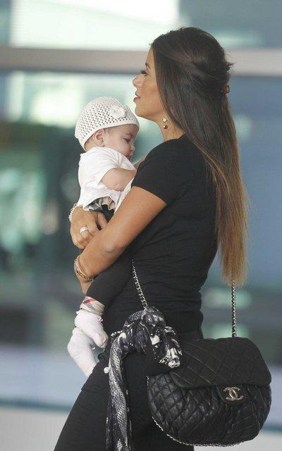 Daniella Semaan, bạn gái hơn 13 tuổi của Fabregas cũng bế cô con gái nhỏ Lia tới sân bay. Người đẹp ba con chơi rất thân với bạn gái Messi nên cả hai rủ nhau đi cùng.
